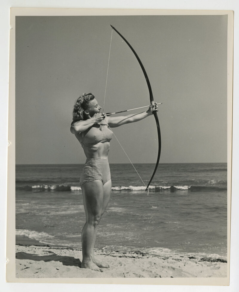 Pudgy shooting a bow and arrow on the beach