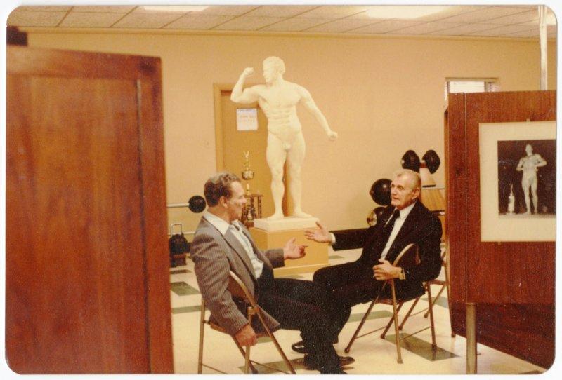 Two men talking beside cast of Sandow
