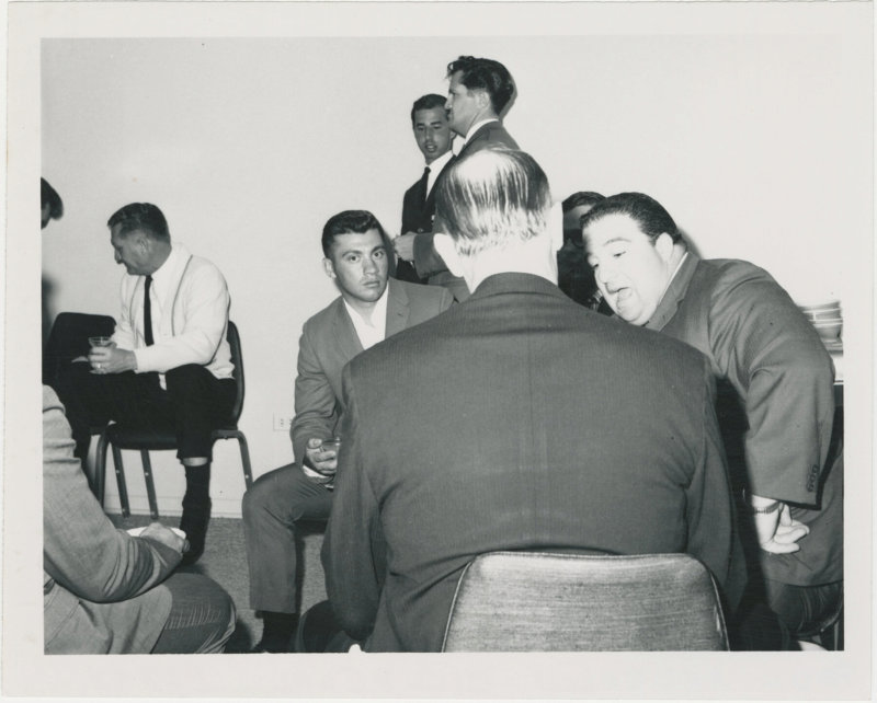 Photo of Paul Anderson conversing with other men at a party